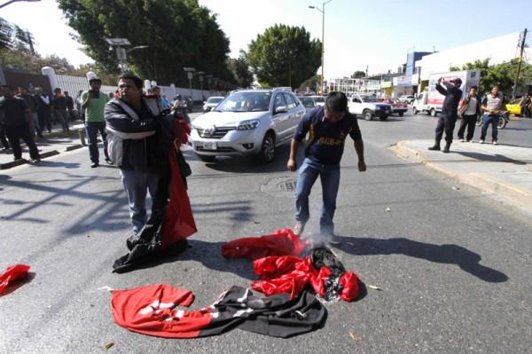 Queman banderas en rechazo a huelga del STAUO